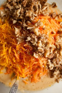 Adding grated carrots, orange zest, and chopped walnuts to the mixture for making Carrot, Walnut and Orange Cake