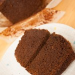 A slice of Jamaica Ginger Cake cut into two on a plate, with the cake in the background.