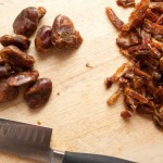 Wooden chopping board with a pile of chopped dates on one side, and a pile of unchopped dates on the other. Below the dates is a sharp knife.
