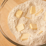 Glass bowl with flour and pieces of margarine.