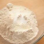 Flour, fast action yeast, salt, and dried milk powder in a glass bowl before mixing.