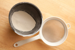 Bowl with sifted flour in it next to a sieve