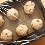 Yorkshire teacake dough rounds in a tin covered in plastic wrap, ready for proofing.