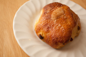 A Bath Bun on a white plate.