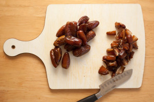 Chopping board with unchopped dates on one half and chopped dates on the other half. A knife is near the bottom.