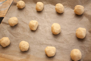Grantham Gingerbread dough balls on a baking sheet ready for baking. The cookie dough balls are placed on a non-stick tray liner.